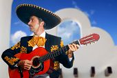 Charro Mariachi singer playing guitar in Mexico with white house background poster