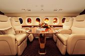 Luxury interior in bright colors of genuine leather in the business jet, sky, clouds and sunset through the porthole poster