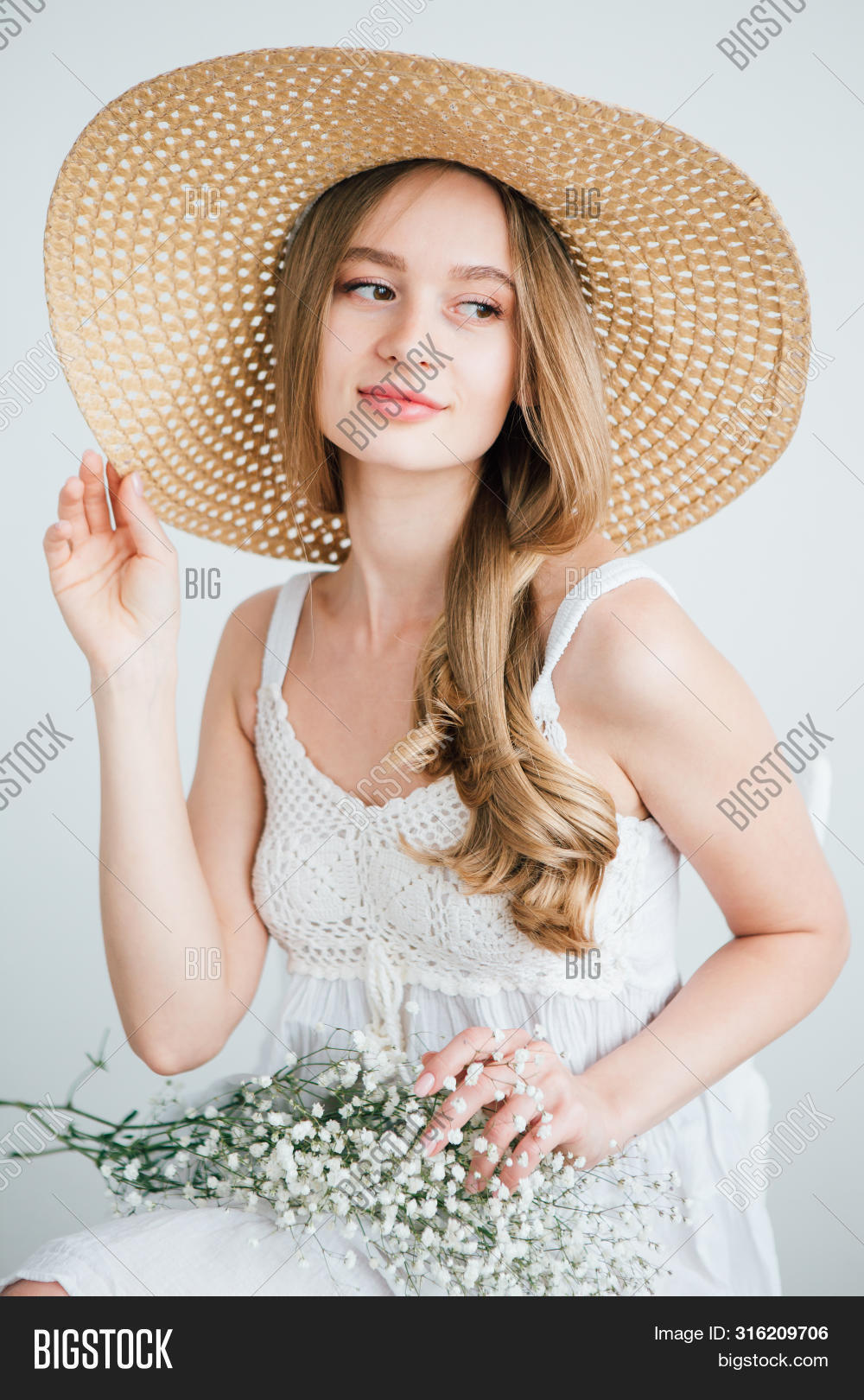 Girl With Long Hair And Hat Posing With A Bouquet Of White Flowers