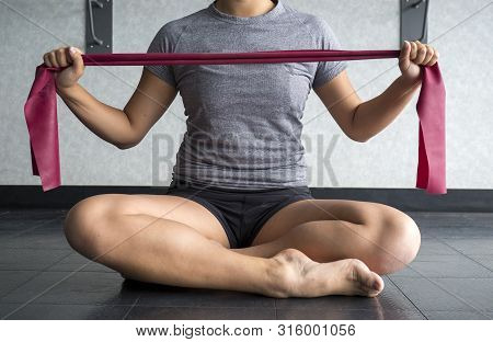 Athlete Holding A Red Thera Band To Exercise And Strengthen Her Arm Muscles With