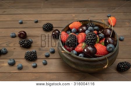 Fresh Raspberry In Small Wooden Bowl On A Wood Background