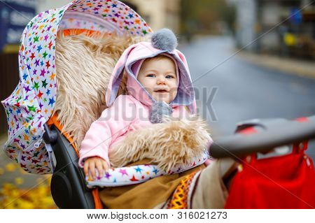 Cute Little Beautiful Baby Girl Sitting In The Pram Or Stroller On Autumn Day. Happy Smiling Child I