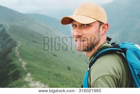 Portrait Of Backpacker Man In Baseball Cap Walking By The Foggy Cloudy Weather Mountain Range Path W