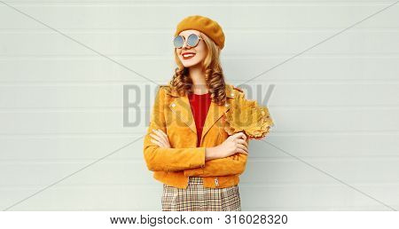 Portrait Smiling Woman With Yellow Maple Leaves Wearing Orange French Beret On City Street Over Gray