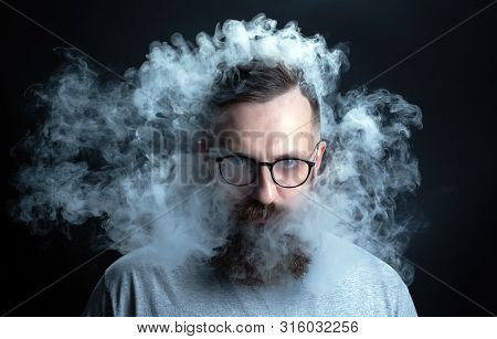 Concept. Smoke Enveloped The Head Man. Portrait Of A Bearded, Stylish Man With Smoke. Secondhand Smo