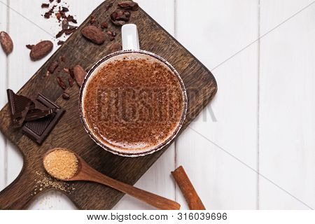Hot Chocolate In The Cup, Cocoa Beans And Powder On The White Wooden Table
