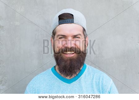 Keeping Hair Healthy. Happy Hipster With Shaped Beard And Styled Hair Wearing Baseball Cap. Bearded