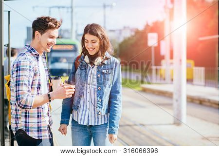 Young Happy Laughing Couple Standing On Tram Stop In Sunny Summer Day. City Public Transport Infrast