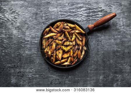 Fried Hot Potatoes In A Pan, Spices. White Sauce. Potatoes Cooked In A Rustic Style. Dark Background