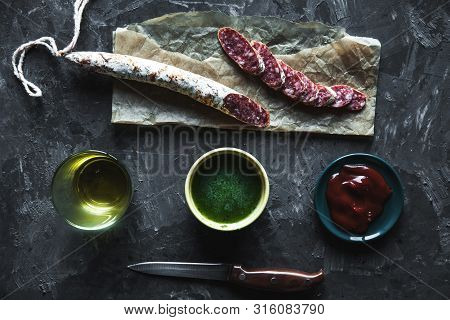 Sausage On A Dark Background With Elements Of Cooking. Cucumber, Onion, Ketchup A
