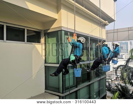 Rope Access Cleaning Worker Wearing Safety Harness Hard Hat Working At Height Descending On Rope Per