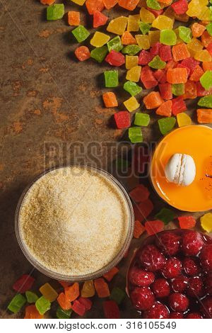 Gelatin and candied fruit. Top view on brown background poster