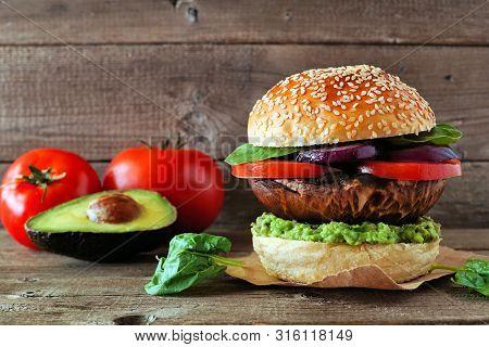 Portobello Mushroom Vegan Burger With Avocado, Tomato, Spinach And Onion Against A Dark Wood Backgro