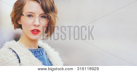 Close-up Portrait Of Young Beautiful Brunette Woman Wearing Glasses. Smart Modern Hipster Girl Eyewe