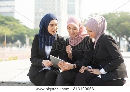 Group of Muslim business women discussing, using tablet pc outdoor.