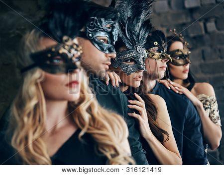 Group Of People In Masquerade Carnival Mask Posing In Studio. Beautiful Women And Men Wearing Veneti