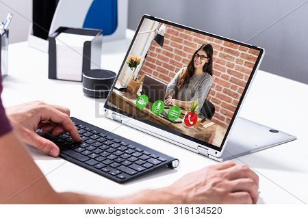 Businessman Video Conferencing With His Colleague On Hybrid Laptop On Desk In Office