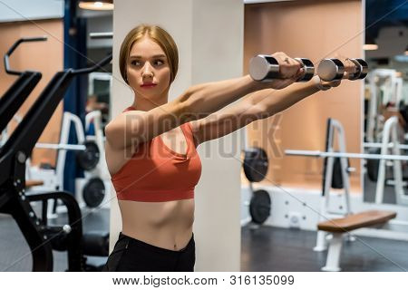 Beautiful Young Woman Trains Deltoid In Gym