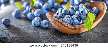 Freshly Picked Blueberries on Dark Slate Background. Juicy and Fresh Blueberries with Green Leaves. Concept for Healthy Eating