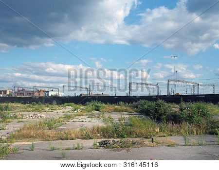 A Large Unused Urban Brownfield Site With Open Land Covered In Cracked Overgrown Concrete Awaiting D