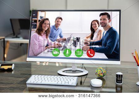Computer Desktop Showing Videoconferencing Application On Office Desk