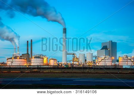 Oil Refinery Industry At Night In Rotterdam, Netherlands. Pollution Smoke From Oil Refinery Industry