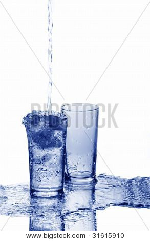 A Glass Is Overfilled With Water And An Empty Glass