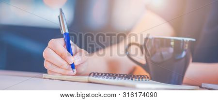 Woman Hand Is Writing On A Notebook With A Pen In Office.web Banner.