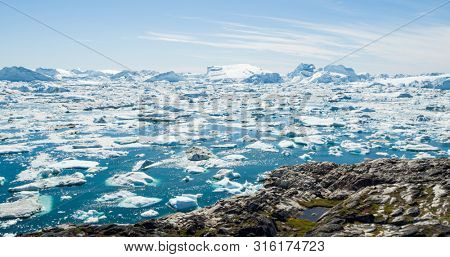 Arctic nature landscape with icebergs in Greenland icefjord. Aerial drone photo image of ice and iceberg. Ilulissat Icefjord with icebergs from Jakobshavn Glacier aka Sermeq Kujalleq glacier.