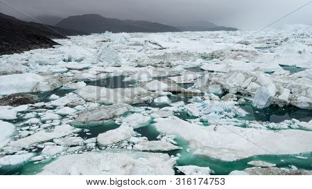 Iceberg in arctic landscape nature with icebergs and ice in Greenland icefjord. Aerial drone photo image of ice and iceberg. Ilulissat Icefjord with icebergs from glacier.