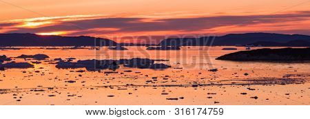 Arctic nature landscape with icebergs in Greenland icefjord with midnight sun sunset / sunrise in the horizon. Aerial drone photo image of ice. Ilulissat Icefjord with icebergs from glacier.