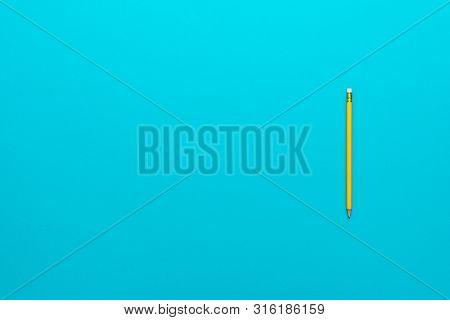 Top View Of Pencil On The Blue Background. Minimalist Flat Lay Photo Of Yellow Pencil Over Turquoise