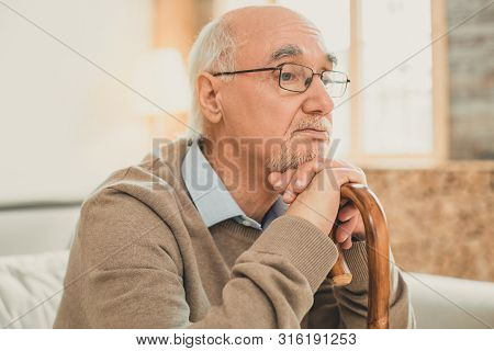 Neat partly-bald old man thoughtfully relying on the wooden stick poster