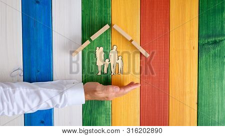 Male Hand Below A Paper Cut Silhouette Of A Family Of Five Under A Roof Of Wooden Pegs In A Conceptu