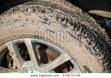 Dirty 4x4 SUV car wheel with light alloy disc, closeup photo, off-road racing theme poster