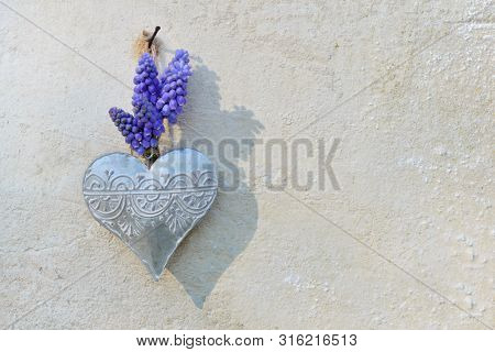 spring flowers and  iron heart hung on a outdoor wall poster