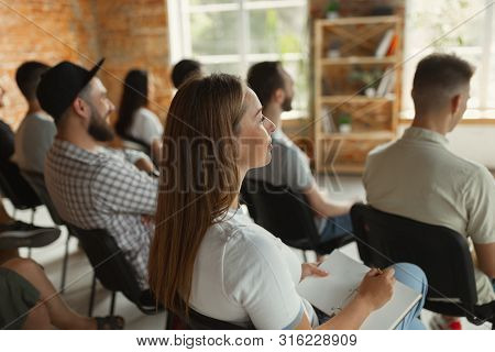 Group Of Students Listen To Presentation At University Workshop. Audience Or Modern Conference Hall.
