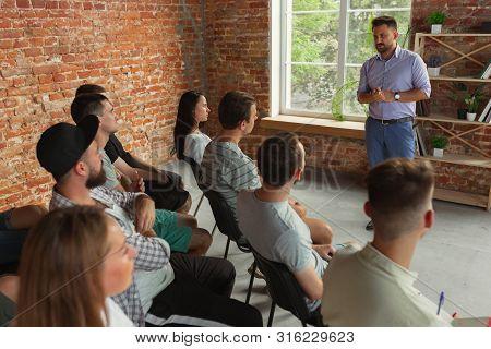 Male Speaker Giving Presentation In Hall At University Workshop. Audience Or Conference Hall. Rear V