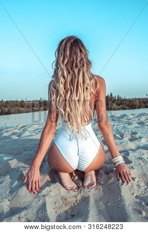 Beautiful Blonde In A White Bodysuit, Summer On A Sandy Beach, View From The Back, Tanned Figure, We