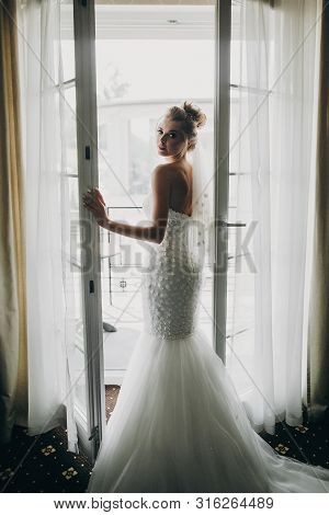 Stylish Bride Opening Window Balcony In Soft Light In Hotel Room. Back Of Gorgeous Sensual Bride In