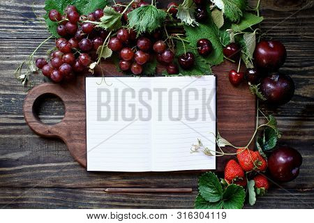 Beautiful Solid Walnut Cutting Board With Open Cookbook And Fresh, Red, Organic Homegrown Fruit. Plu