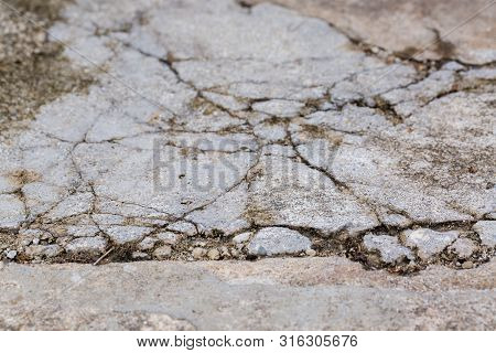 Worn And Cracked Asphalt With Big Cracks. Old Road Concrete Texture With Cracks. Cement Cracked Back