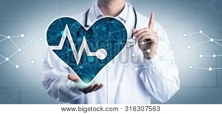 Young Cardiologist Holding A Virtual Heart Displaying A Pulse Trace In The Open Palm Of His Right Ha