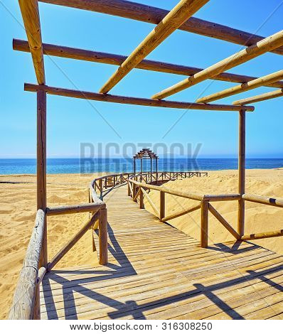 Wooden Boardwalk Going To A Broad Beach Of Fine Sand Dunes With The Sea In The Background On A Sunny