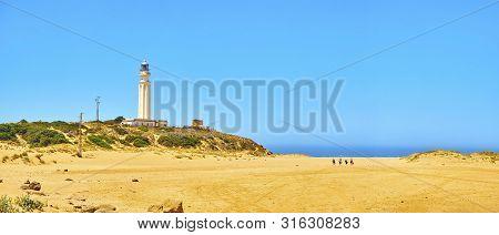 Tourists Walking In Direction To Faro De Trafalgar Beach, A Broad Beach Of The Cabo De Trafalgar Cap