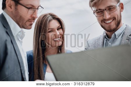 close up. smiling business team looks at the laptop screen