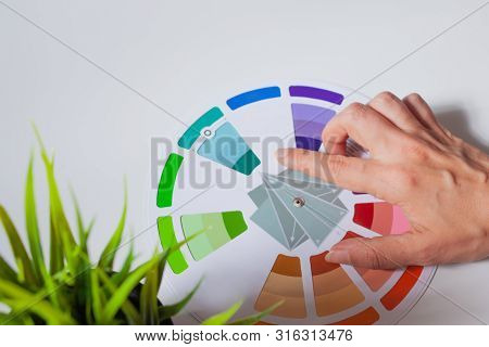 Define Your Color Type. Female Hands With Neat, Concise Manicure Rotate The Color Wheel. The Color C