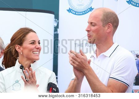 COWES, ENGLAND. 08 AUGUST 2019: Catherine, Duchess of Cambridge looks on as Prince William The Duke of Cambridge pokes his tongue out, during the SailGP race weekend held in Cowes, Isles of Wight, UK.