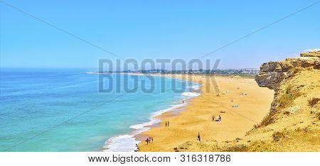 Barbate, Spain - June 26, 2019. People Enjoying A Sunbathing In The Faro De Trafalgar Beach, A Broad