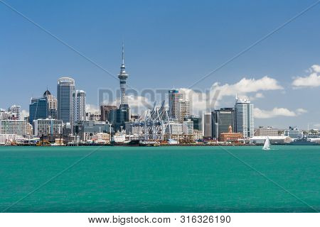 Auckland, New Zealand - December 9, 2012: Auckland Skyline With Sailboat And Blue Sky